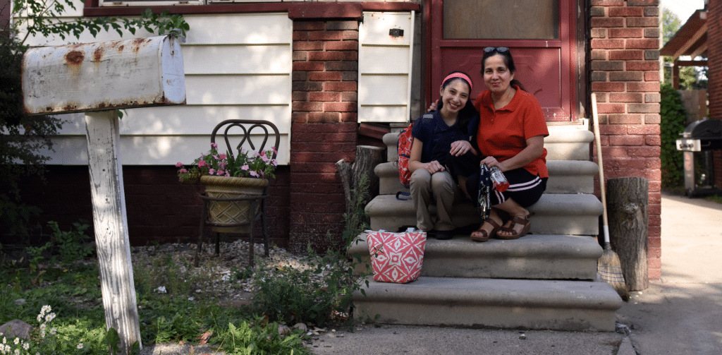 Mayra and daughter on steps of their home