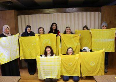 women holding up yellow fabric